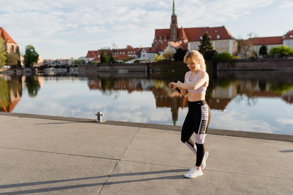 Marta Kruk z Codziennie fit jest nad rzeką i sprawdza swój zegarek sportowy Polar